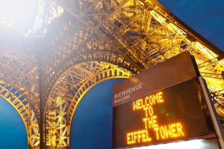 PARIS, FRANCE - SEPTEMBER 3: Low angle detailed view of Eiffel tower base with welcoming sign. Night shot, dark blue sky in background. September 3, 2011, Paris, France, Europe.