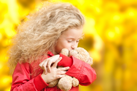 Beautiful and happy little girl with teddy bear on her hands. Kissing her toy with her eyes closed. Yellow autumn trees in background. photo