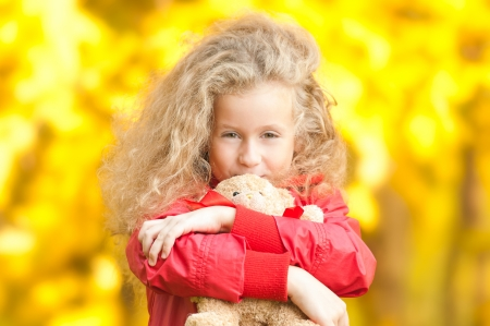 Beautiful and happy little girl with teddy bear on her hands. Smiling and looking into the camera. Yellow autumn trees in background. photo