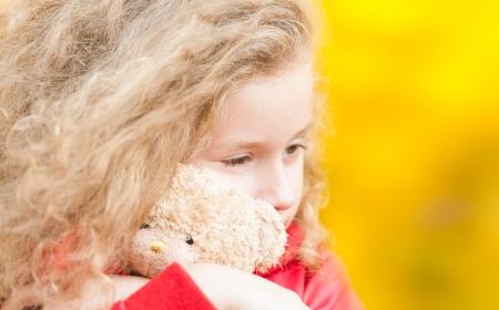 Beautiful and sad little girl hugging teddy bear.  photo