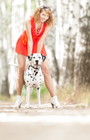 Beautiful and sexy young woman in red dress with dalmatian dog in summer forest. photo