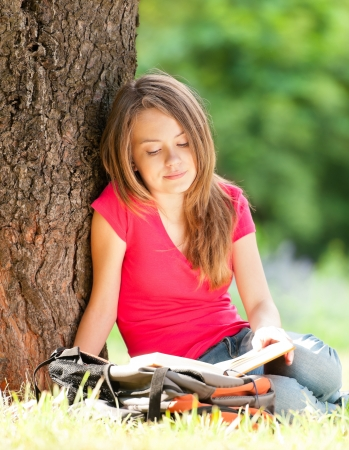 beautiful and happy young student girl sitting on green grass under the tree, smiling and reading book.  Stock Photo
