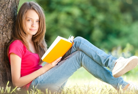 ツリーの下に緑の草の上に座って美しい、幸せな若い学生の女の子 写真素材