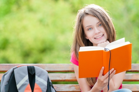 beautiful and happy young student girl sitting on bench, holding book in her hands 版權商用圖片