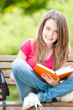 beautiful and happy young student girl sitting on bench, holding book in her hands