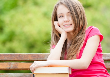 beautiful and happy young student girl sitting on bench, her hands on pile of books, looking into the camera and smiling.  photo
