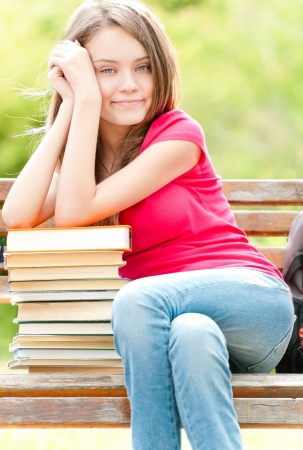 beautiful and happy young student girl sitting on bench, her hands on pile of books photo