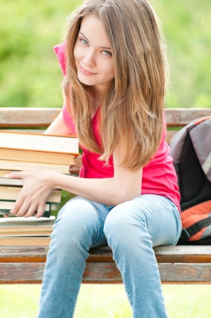 beautiful and happy young student girl sitting on bench and lifting heavy pile of books with her hands photo