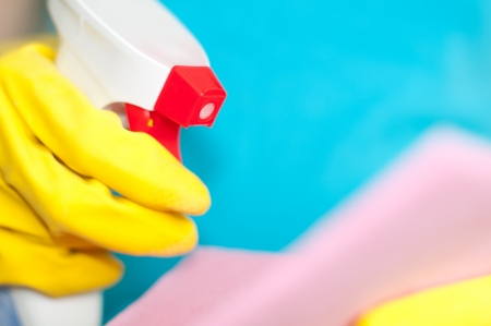 household objects equipment: woman in protective yellow gloves holding sprayer and duster in her hands (shallow depth of field, focus on the nose of the sprayer)