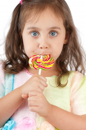 girl licking: beautiful and cute little girl eating colorful lollipop and looking into the camera. Studio shot, isolated on white background