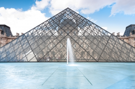 FRANCE, PARIS -  SEPTEMBER 5: Glass pyramid of Louvre museum, main entrance to the museum, fountain in foreground and blue sky with clouds in background. SEPTEMBER 5, PARIS, FRANCE, EUROPE,