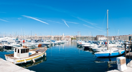 Panorama of the port of Marseille (Marseilles). Small private boats in foreground with deep blue water of the harbor, blue sky in background.
