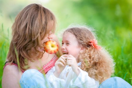 Beautiful and  happy young mother eating apple together with her small daughter. Summer park in background photo