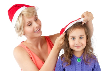beautiful and happy young mother putting on christmas santa hat on her daughter.  photo