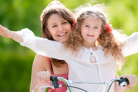 Beautiful and happy young mother on bicycle with her daughter. Both smiling, summer park in background. photo