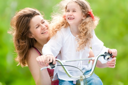 child couple: Beautiful and happy young on bicycle with her daughter. Both smiling, summer park in background. Stock Photo