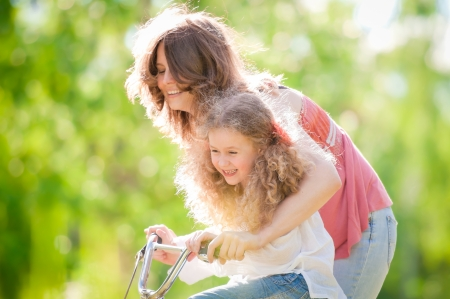 Beautiful and happy young mother teaching her daughter to ride a bicycle. Both smiling, summer park in background. 版權商用圖片