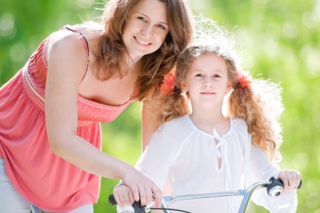 Beautiful and happy young mother teaching her daughter to ride a bicycle. Both smiling and looking into the camera. Summer park in background. photo