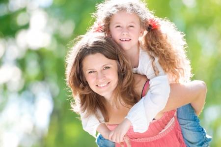 Mooi en gelukkig jonge moeder die piggyback rit aan haar dochter. Zowel glimlachen en kijken naar de camera. Zomer park in achtergrond.