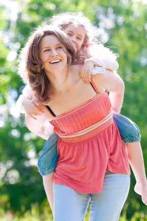 Beautiful and happy young mother giving piggyback ride to her daughter. Both smiling. Summer park in background. photo