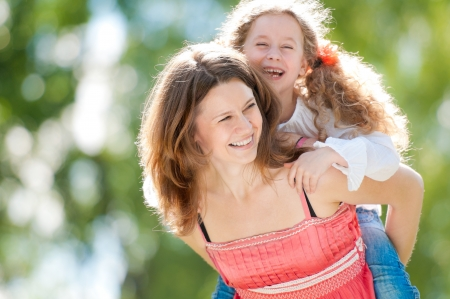 piggyback ride: Beautiful and happy young mother giving piggyback ride to her laughing daughter