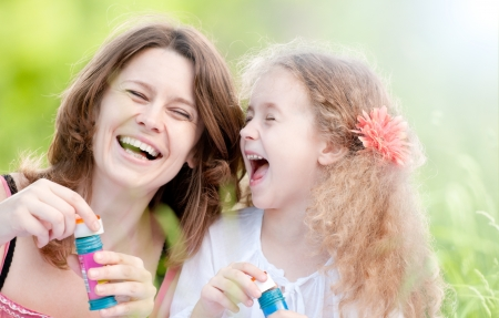 Beautiful young mother together with her daughter in nature making soap bubbles and laughing photo