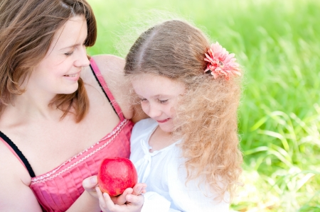 Beautiful and  happy young mother holding apple in her hand together with her small daughter. Summer park in background photo