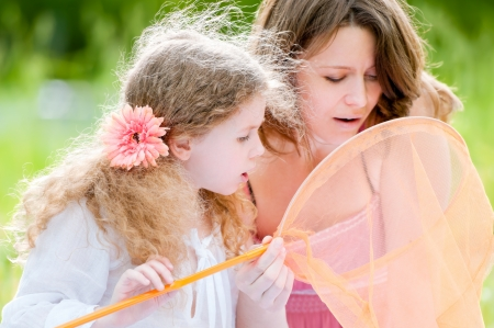beautiful little girl and her mother looking into the butterfly net. Summer park in background. photo