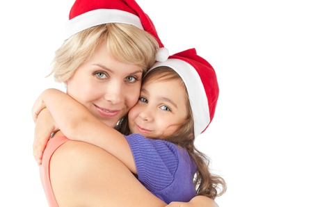 Both mother and daughter wearing christmas santa hats and looking into the camera. photo