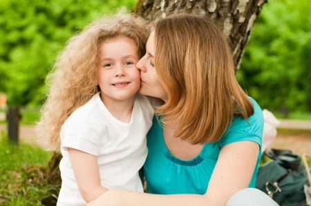 happy young mother sitting in park under tree and kissing her smiling small daughter photo