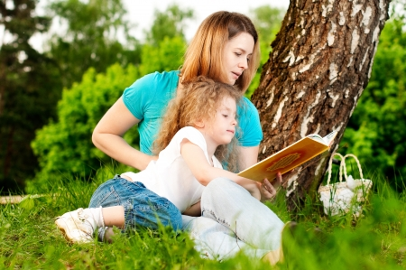 young mother sitting in grass under tree and reading book to her small daughter who is lying on knees of her mother and smiling photo