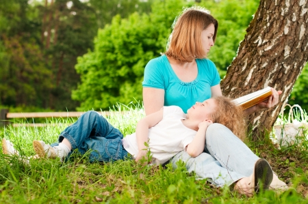 young mother sitting in grass under tree and reading book to her small daughter who is lying on knees of her mother and sleeping photo