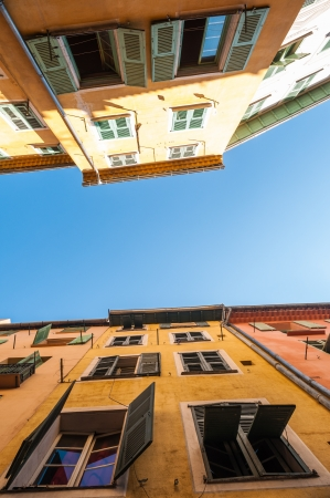 cote d'azur: Two traditional french houses in Nice city on summer sunny day. Clear blue sky above buildings. Cote dAzur, Nice, France, Europe. Stock Photo
