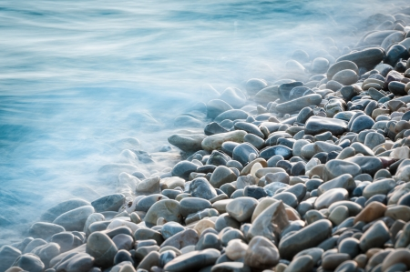 Pebble Beach: pebble stones by the sea. Silky waves of blue sea from long exposure.