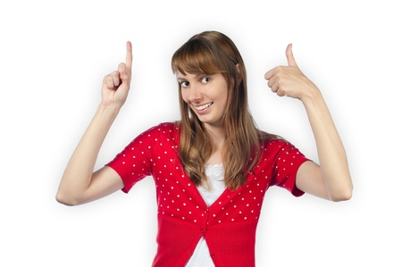 Beautiful and  happy young woman pointing up above herself with one hand and making thumbs up gesture with the other one.  Stock Photo - 15183320