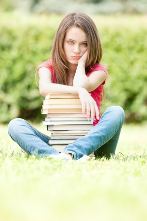 beautiful and sad young student girl sitting on green grass, pile of books under her hands.  photo