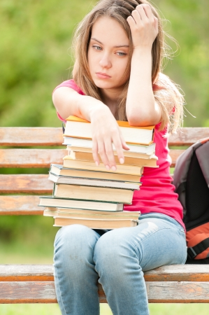 sad young student girl sitting on bench with pile of books under her hands.  photo