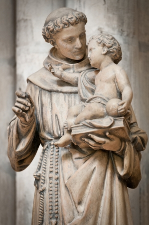 Statue of man holding small boy on his hands. Sculpture from Saint Denis cathedral. Paris, France, Europe.
