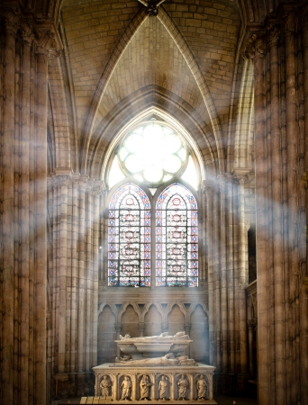stained: sun rays beaming through the old stained glass window of saint denis cathedral and lighting interior with tomb. Paris, France, Europe.