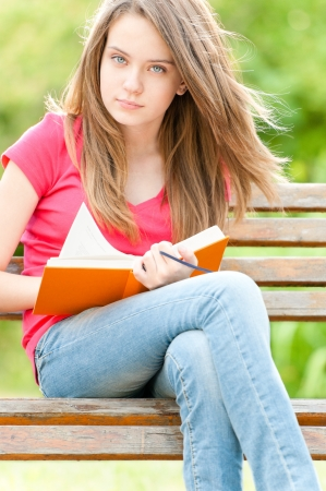 beautiful and serious young student girl sitting on bench, holding book in her hands and looking into the camera. Summer or spring green park in background photo