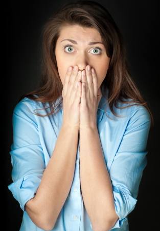 Beautiful and shocked young woman. Problems or bad news. Hands at her face. Looking into the camera, dark background. Stock Photo - 14858672
