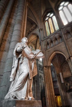 Interior of Saint Denis Basilica with the statue of the man with the book in his hands. Paris, France, Europe.