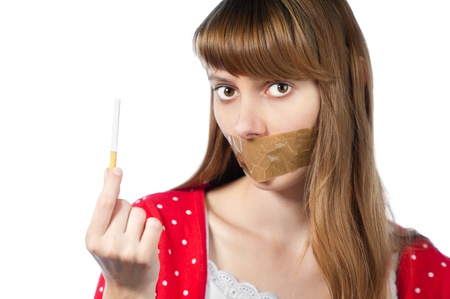 Beautiful young woman with sticky tape on her mouth and cigarette in her hand. Looking into the camera. Stop smoking concept. Isolated on white background photo