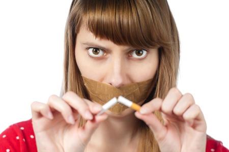 Beautiful young woman with sticky tape on her mouth and broken cigarette in her hands. photo