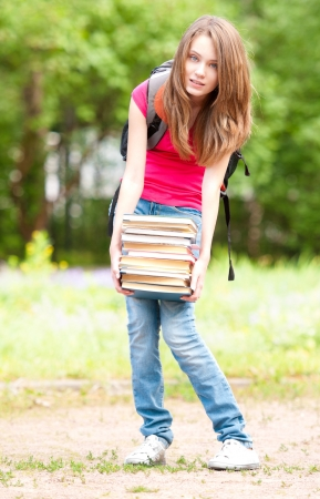 beautiful young student girl standing in park and holding pile of heavy books in her hands. Looking into the camera. Summer or spring green park in background photo