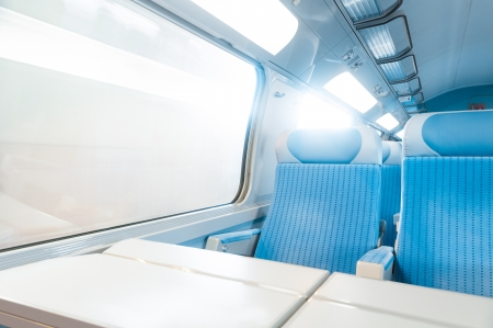 Inside cabin of modern express train. Nobody in blue chairs at window. Motion blur. Comfortable chairs and table in foreground, sun in background. Travel, France, Europe.