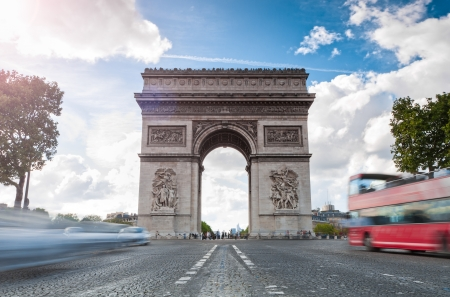 Triumphal arch. Blue sky and white clouds in background. Blurred cars and red tourist bus in foreground. Paris, France, Europe. photo