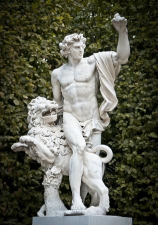 versailles: Classic sculpture in garden of Versailles. Beautiful young man with lion. Versailles, Paris, France, Europe. Editorial