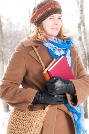 winter street portrait of young beautiful natural looking woman in casual clothes holding books and smiling photo