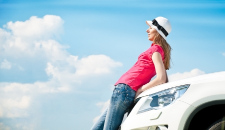 Beautiful young woman resting at bonnet of her car with her eyes closed and blue cloudy sky in background